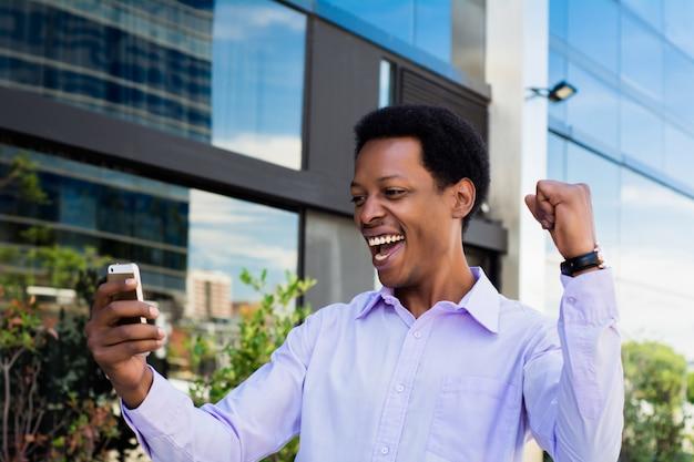 Бизнесмен взволнован, глядя на мобильный телефон