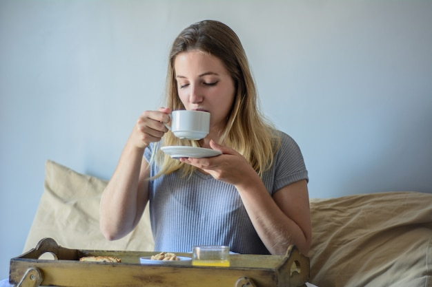 Молодая женщина в постели, едят завтрак