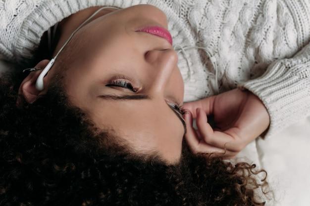 ベッドで音楽を楽しむ若い女性