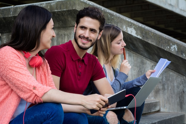 屋外で一緒に勉強している大学生のグループ