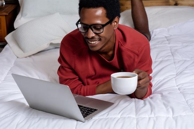 若い男がベッドで彼のラップトップを使用して
