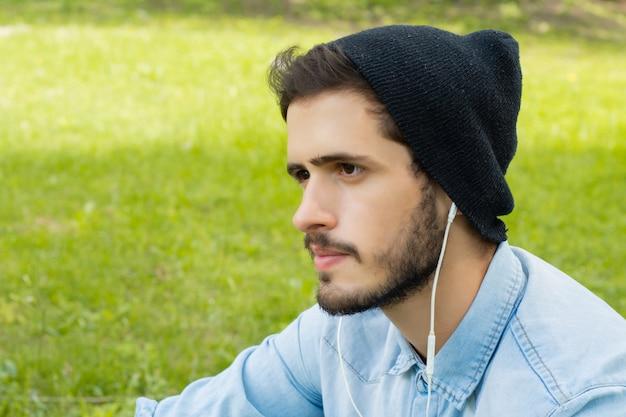 Молодой человек слушает музыку в наушниках