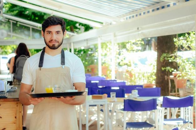 Молодой официант держит поднос.