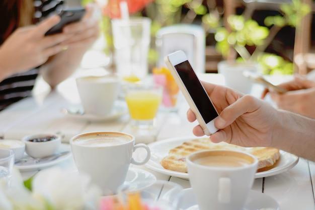 Друзья с помощью смартфона кафе.