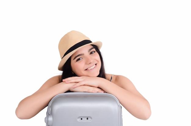 スーツケースを持つ若い観光客女性。