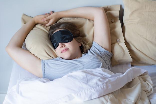 目を覚ます若い女性