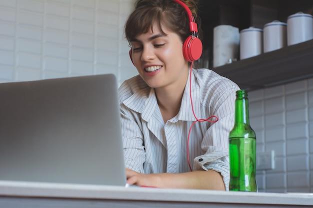 Молодая женщина с пивом и с помощью своего ноутбука