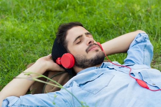 リラックスして、芝生の上の音楽を聴く若い男。