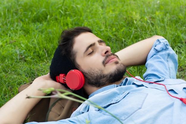 Молодой человек расслабляющий и слушать музыку на траве.