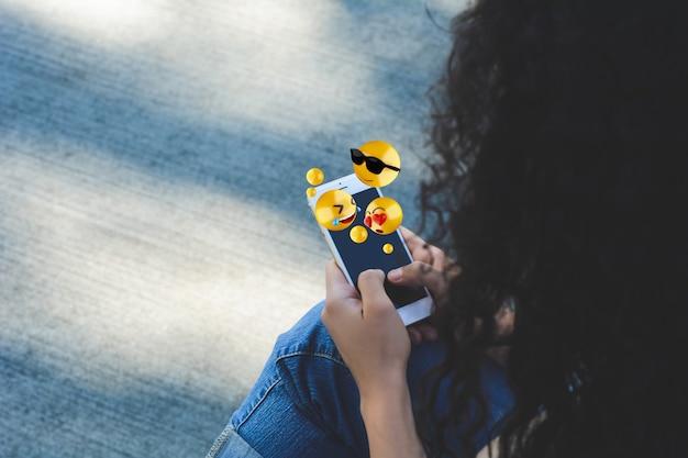 絵文字を送信するスマートフォンを使用して女性。