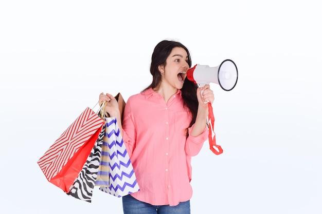 買い物袋とメガホンを保持している女性