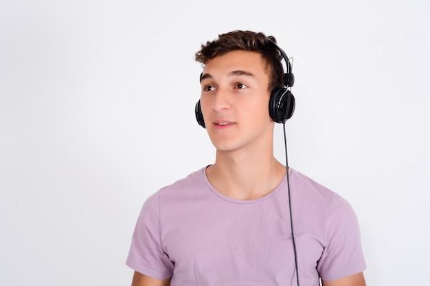 Портрет улыбающегося подростка, слушающего музыку в наушниках