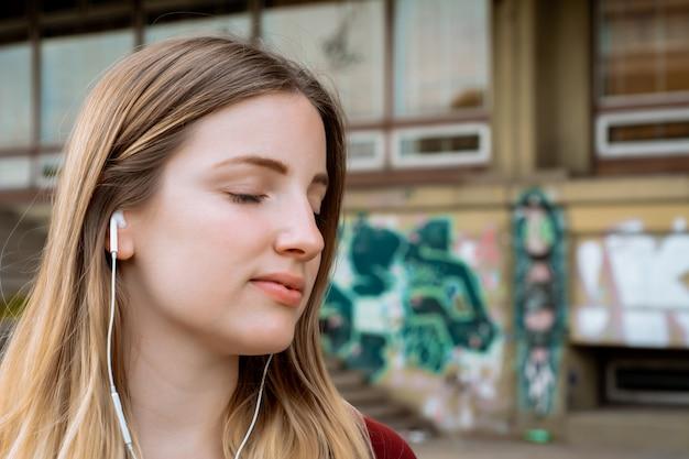 Молодая белокурая женщина слушая к музыке с наушниками