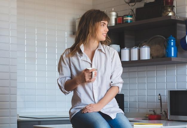 Молодая женщина пьет кофе у себя дома