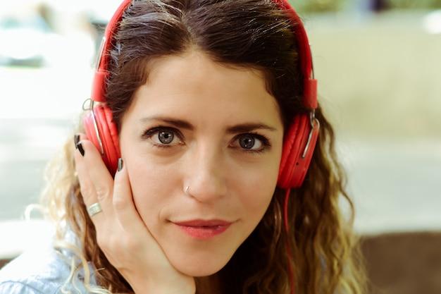 ヘッドフォンで音楽を聴く若い女性。