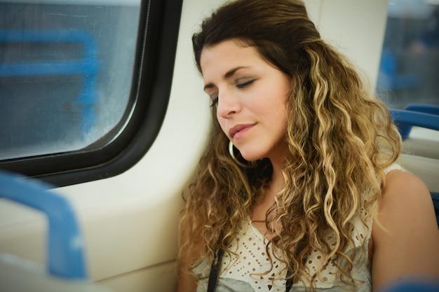 Городская женщина спать в путешествии на поезде около окна.