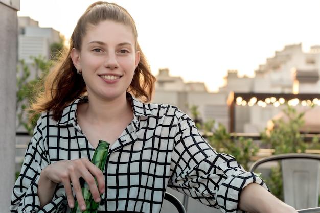 屋外の屋上で飲む若い女性