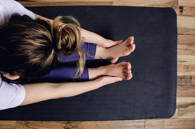 若い女性が家でヨガを練習します。