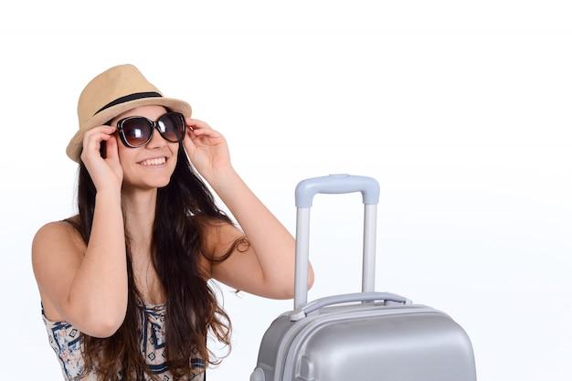スーツケースとサングラスの若い観光客女性