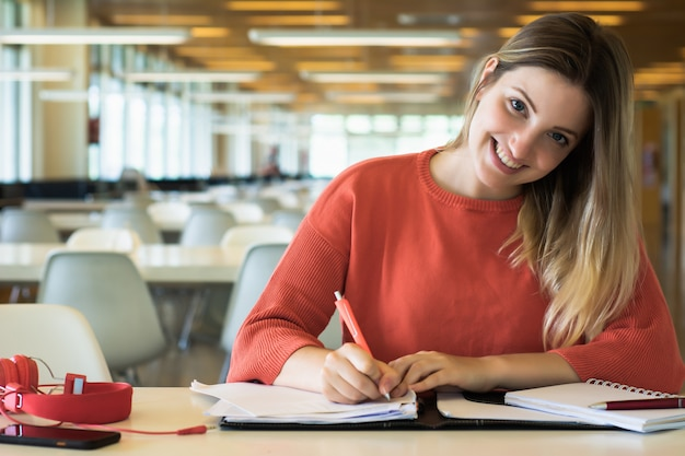 図書館で勉強している若い女子学生。