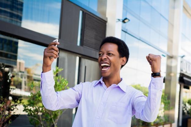 ビジネスマンは携帯電話を見て興奮しています。