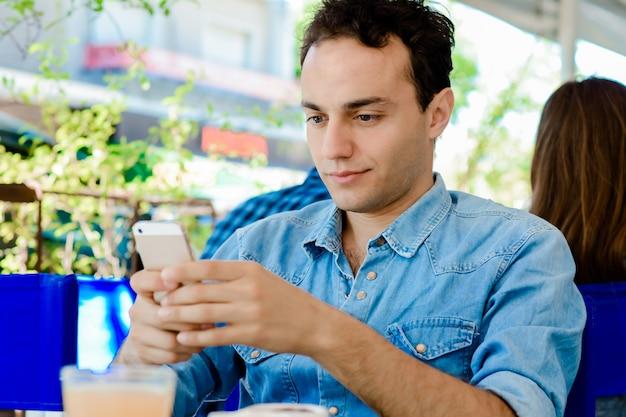 携帯電話を使用して、コーヒーを飲む人
