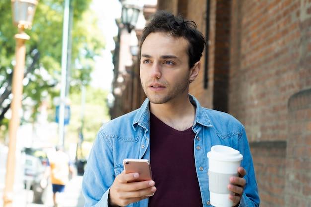 Сообщение молодого человека печатая с мобильным телефоном