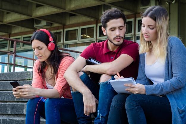 屋外で一緒に勉強する大学生のグループ