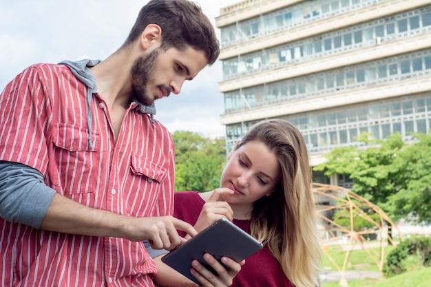 Двое студентов университета вместе учатся на улице