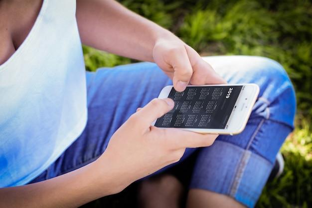 Женщина держит смартфон с приложением календаря