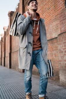 若い男が通りを歩きながら買い物袋を保持しています。