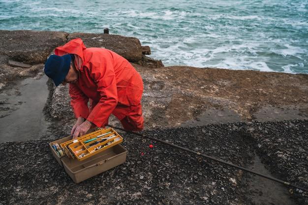 Рыбак с коробкой рыболовного снаряжения.