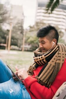 アジア人の男性が彼のデジタルタブレットを使用しています。