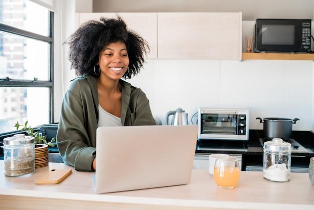 自宅でラップトップを使用してラテン女性。