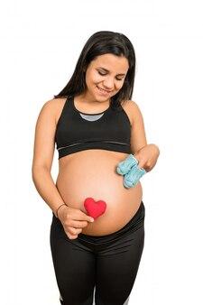 妊娠中の女性が腹にベビーソックスを保持しています。