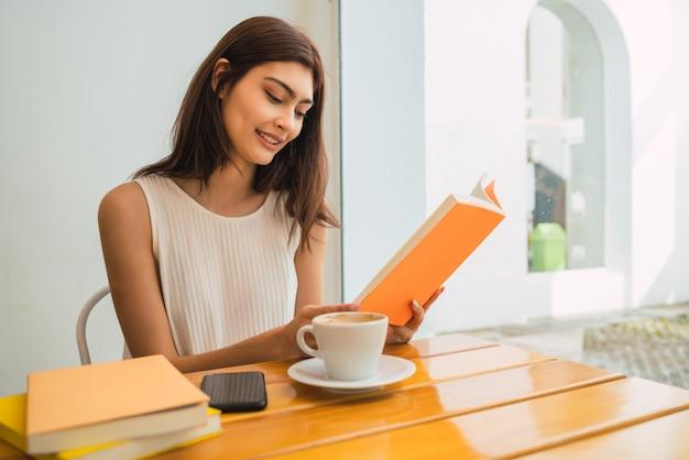 Молодая женщина читает книгу в кафе.