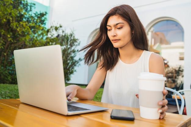 コーヒーショップでラップトップを使用して若い女性。