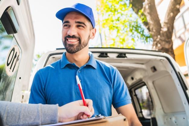 Пакет нося работника доставляющего покупки на дом пока клиент подписывает внутри доску сзажимом для бумаги.