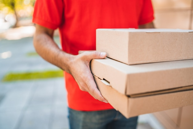 Доставка человек, перевозящих пакеты во время доставки на дом.