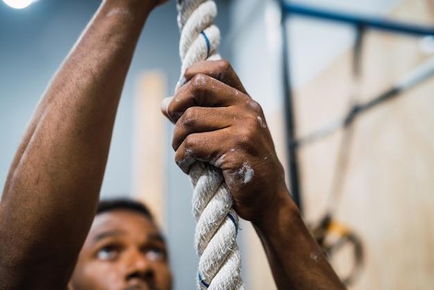 Спортивная (ый) человек делает упражнения на скалолазание.