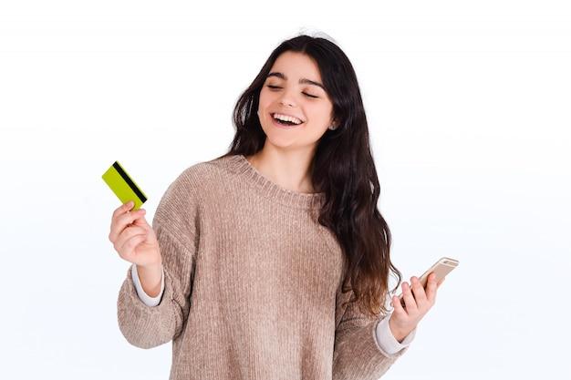 クレジットカードとスマートフォンを持つ女性。