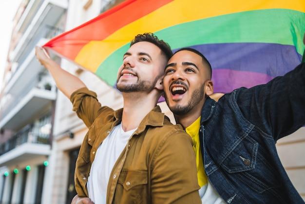 Гей-пара обнимает и показывает свою любовь с радужным флагом
