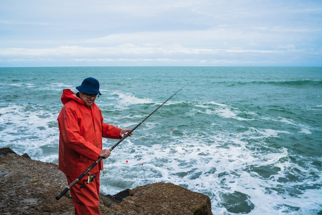 Старик рыбалка в море