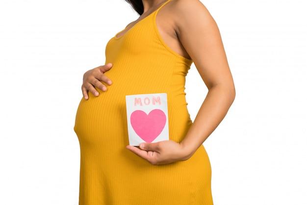 妊娠中の女性がグリーティングカードを保持しています。