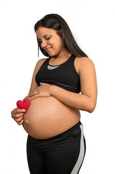 妊娠中の女性の腹に心のサインを保持しています。