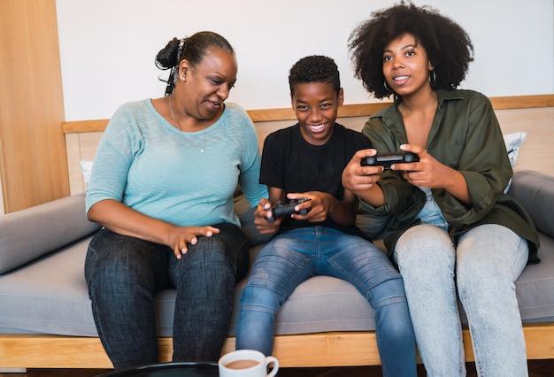 Бабушка, мама и сын играют в видео игры дома.