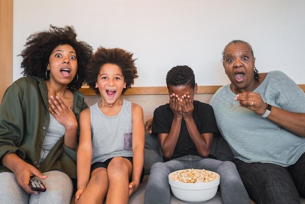 祖母、母、子供たちが家で映画を見ています。