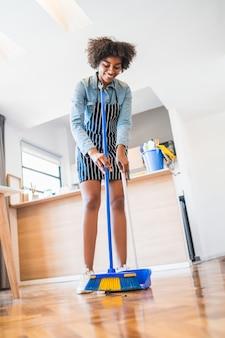自宅でほうきで床を掃除するアフロの女性。