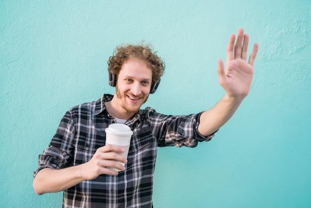 Человек, махнув рукой и улыбаясь, поздороваться с кем-то.