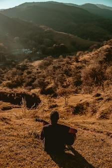 山のバックライトでギターを持つ男